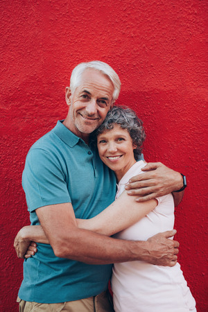 embracing couple: Portrait of beautiful senior couple embracing against red background. Loving mature couple standing together.