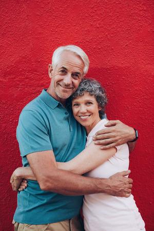 pareja abrazada: Retrato de la hermosa pareja de ancianos abrazando contra el fondo rojo. Amantes de la pareja madura de pie juntos.