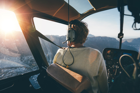 Achter mening van vrouwelijke toerist op helikopter kijken uit het raam. Helikopter passagiers genieten van het uitzicht.