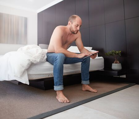 man sit: Handsome young man using a digital tablet, he is sitting shirtless on the edge of his bed.