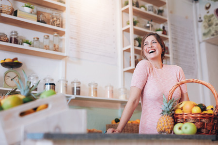 juice bar: Portrait of beautiful young woman standing at a juice bar counter and looking away smiling. Successful female juice bar owner. Stock Photo