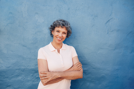 person: Portrait of attractive mature woman with her arms crossed standing against blue background. She is leaning to a blue wall with copy space.