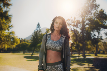 middle eastern woman: Portrait of confident woman in sportswear at the park. Young middle eastern woman standing outdoors on sunny morning and looking at camera. Stock Photo