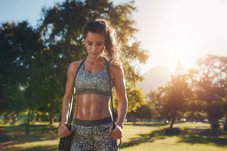 Fit and athletic young woman standing in a park with a jump rope. Young woman aerobics instructor with jumprope.