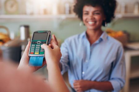 client Femme paiement par carte de crédit au bar à jus. Focus sur les mains de femme entrant dans la broche de sécurité dans le lecteur de carte de crédit.