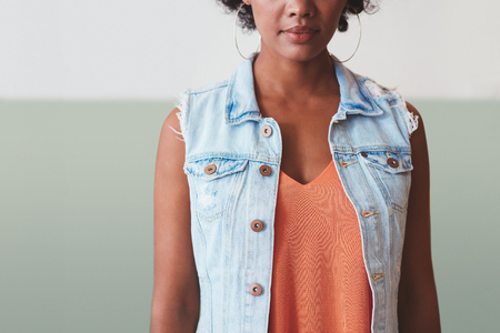 casuals: Cropped image of young african woman in stylish casuals. She is wearing a sleeveless denim shirt.