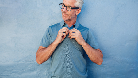 buttoning: Portrait of mature man buttoning up his tshirt, he is standing against a wall and looking away.