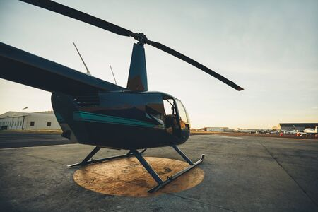 Civilian helicopter parked at the helipad in airfield