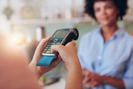 주스 바에서 신용 카드로 지불하는 젊은 여자. 신용 카드 판독기에 보안 핀을 입력하는 여자 손에 초점을 맞 춥니 다. 스톡 콘텐츠
