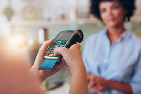 Young woman paying by credit card at juice bar. Focus on woman hands entering security pin in credit card reader. Reklamní fotografie - 56933937