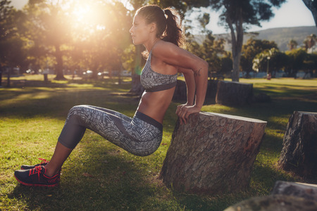 Young woman practicing push ups in a park. Side view shot of muscular female exercising with a log.