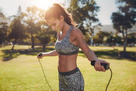 Portrait der jungen Frau passen mit Springseil in einem Park. Fitness weiblich macht sich im Freien an einem sonnigen Tag Training zu überspringen.