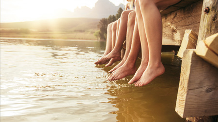 Four young friends sitting on jetting with their legs hanging down to the water on a summer day. Focus on legs of young people. Stock Photo