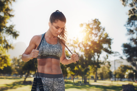 woman rope: Fit young woman holding a skipping rope around her neck. Female athlete taking a break from fitness training at the park.