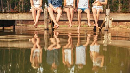 jetty: Legs of young people sitting on the edge of a jetty hanging down to the water. Group of friends hanging out at the lake. Stock Photo