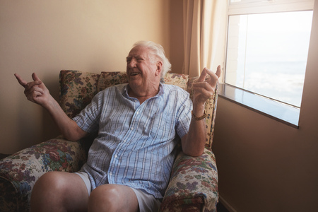 old age home: Indoor shot of happy old man sitting on a arm chair and  smiling. Senior man relaxing at old age home.