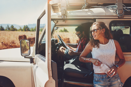 weekend break: Young woman standing outside the car holding a water bottle with man sitting on driving seat looking at a the road map. Couple on a road trip taking a break.