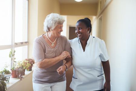 Retrato do sorriso cuidador domiciliar e mulher sênior que andam junto através de um corredor. Trabalhador dos cuidados médicos cuidando da mulher idosa.