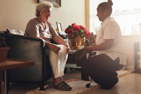 Mujer mayor que se sienta en una silla en su casa con mujer cuidadora sosteniendo la presión arterial. enfermera de sexo femenino que visita el paciente mayor para el control de la presión arterial.