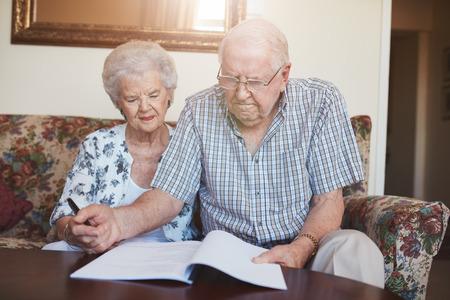 Portret van een gepensioneerd paar die over documenten kijken terwijl thuis het zitten. Hogere Kaukasische man en vrouwenzitting op bank en het ondertekenen van wat administratie.