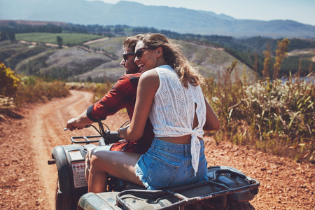 Rear view shot of young couple riding on a quad bike in countryside and looking away smiling. Woman sitting behind her boyfriend driving an quad on country road. photo