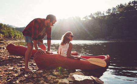 piragua: Hombre joven que empuja una canoa en el agua, mientras que una mujer se sienta en la canoa. Pares que van a para navegar en kayak en el lago en un día de verano.