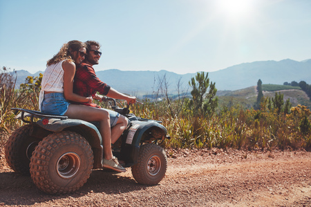 Happy young couple in nature on a quad bike. Young man and woman enjoying a quad bike ride in countryside. photo