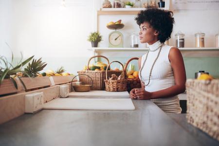 jugo de frutas: Retrato de la cara de una mujer joven y bella detrás del mostrador bar de zumos. dueño de un bar de zumo de fruta de sexo femenino africano.