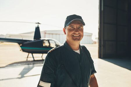 Portrait of happy male pilot standing in airplane hangar with a helicopter in background Stok Fotoğraf