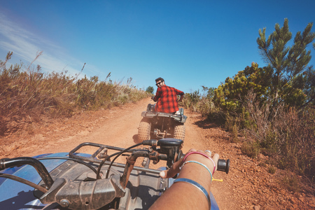 quad: Young man driving a quad bike on country road. Young man on an all terrain vehicle in nature. POV shot.