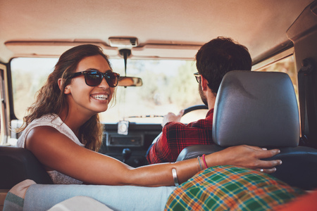 Happy young woman looking back with man driving car. Couple in a car going on roadtrip. photo