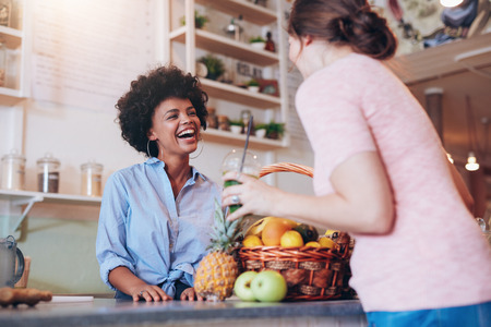 Portrait of young african woman standing behind juice bar counter and talking with female customer holding a glass of fresh juice. Stock Photo