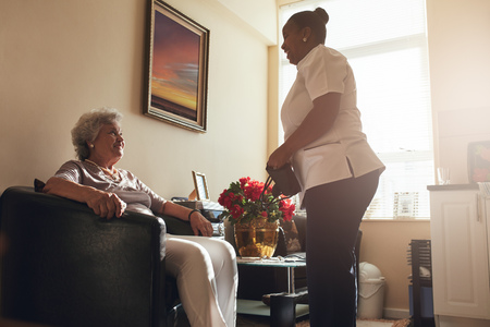 social work aged care: Senior woman sitting on a chair at home with female caregiver standing by. Female nurse visiting senior patient for checking blood pressure.