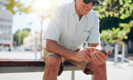 messages: Cropped portrait of smiling mature man using mobile phone while sitting outdoors on a bench in the city