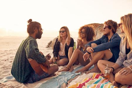 Gruppo di amici di relax a una festa sulla spiaggia al tramonto con il giovane uomo che suona una chitarra. Giovani che hanno una festa sulla spiaggia. Archivio Fotografico