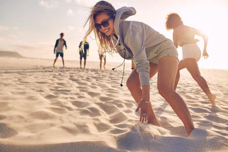 Mladá žena běží závod na pláži s přáteli. Skupina mladých lidí, kteří hrají hry na písečné pláži v letním dni. Reklamní fotografie