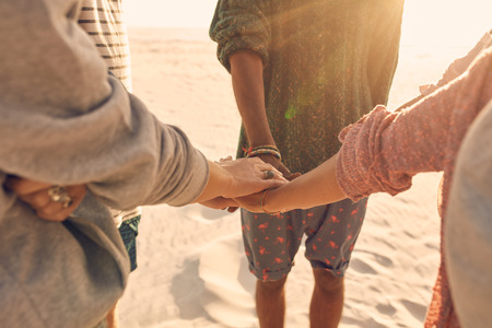 Group of friends stack their hands together. Young men and women standing together at the beach stacking their hands, concept of unity and teamwork. photo