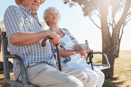 Senior paar zittend op een bankje met wandelstok. Bejaard paar die in openlucht op een de zomerdag ontspannen.