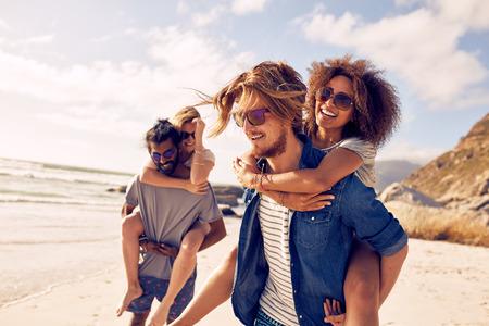 Twee gelukkige jonge mannen geven hun vriendinnen piggyback ritten. Groep van jonge mensen genieten in de zomer op het strand.