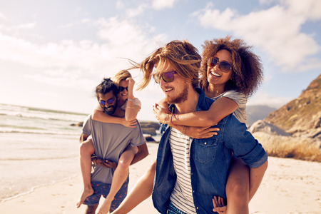 Two happy young men giving their girlfriends piggyback rides. Group of young people enjoying themselves during summertime at the beach. Stock Photo