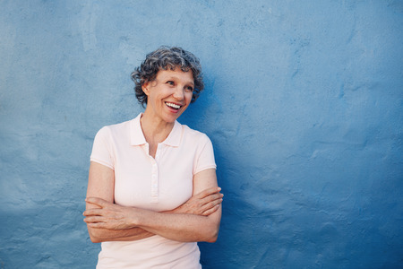 one senior woman only: Portrait of smiling senior woman standing with her arms crossed and looking away at copy space against blue background. Caucasian middle aged female looking happily at copy space.