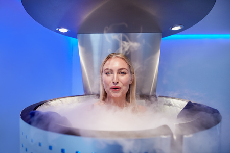 Portrait of happy young woman in a whole body cryotherapy cabin. She is looking at camera and smiling. Stock Photo