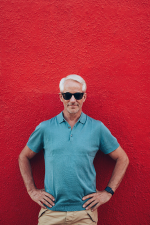stylish hair: Portrait of handsome mature man standing his hands on hips against red wall. Smart middle aged man with glasses on red background. Stock Photo