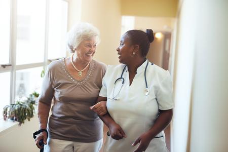 高級女子走在養老院護理員的支持。護士協助年長的女人。