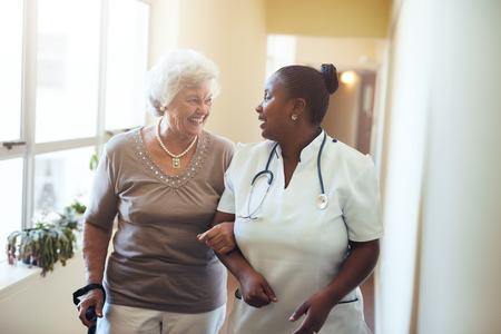 Starszy kobieta spaceru w domu opieki wspierany przez opiekuna. Pielęgniarka pomoc starszych kobiet. Zdjęcie Seryjne