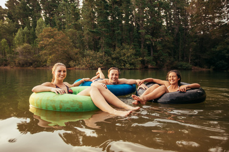 Portrait of happy young adults on inner tubes in lake. Friends enjoying a day at the lake. Stock Photo