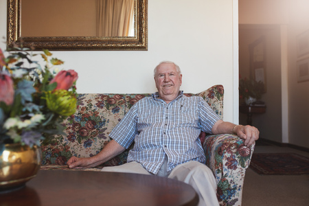 he old: Indoor shot of happy senior man sitting relaxed on a couch at old age home. He is looking at camera and smiling. Stock Photo