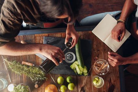Zwei barmen Schaffung neuer Cocktail-Rezept und nehmen Sie sich Notizen. Draufsicht des Menschen einen Cocktail vorbereiten und eine andere nehmen Sie sich Notizen Mischung in einem Jigger Gießen. Standard-Bild - 57548129