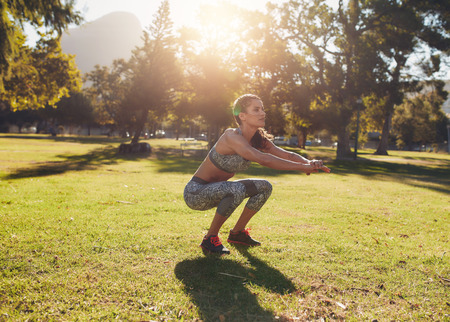 en cuclillas: Full length outdoor shot of fit young woman exercising in park. She doing squatting on a sunny morning.