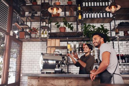 Koffiewinkel werknemers staan aan de balie kijken buiten het cafe en glimlachen.